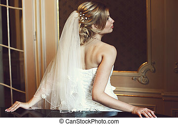 A view from behind on blonde bride leaning on the piano in a hall