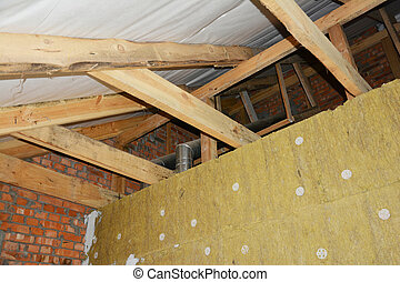A view from inside a house attic construction on unfinished roof with wooden frame, roof beams, rafters, ceiling joists, trusses, vapor barrier installed and a wall with mineral wool insulation.