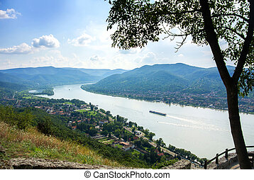 A view from the hill of Visegrad castle to Danube river and a ship, villages and mountains, with a tree at foreground, Visegrad, Hungary.