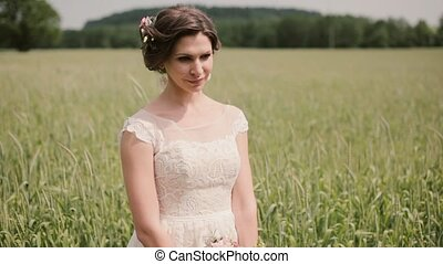 A view of a beautiful bride in a white lacy wedding dress, she holds a bouquet in her hands standing in a wheat field.