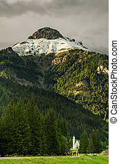 a view of a church with three people walking in atalian alps...