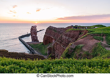 A view of a unique natural phenomenon called Lange Anna, located on the island of Helgoland in Germany in the North Sea. It is a rock rising from the sea. The sun sets on the horizon.