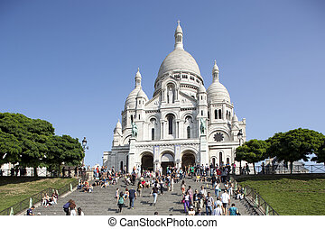 a view of sacre coeur with tourists on the steps