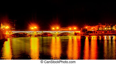 A view of the Guadalquivir River and Puente de Triana, in Seville, Spain at night