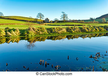 A view of the Lancaster canal with a farm house, bordered by...