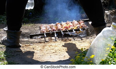 A view of the legs of a man cooking Shish kebab on skewers over a fire in the countryside in the village
