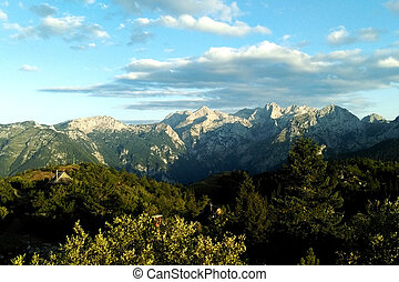 A view of the mountains with green trees and a beautiful sky