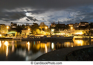 skyline at night of Murten in Switzerland with the harbor and pier and boat in the foreground