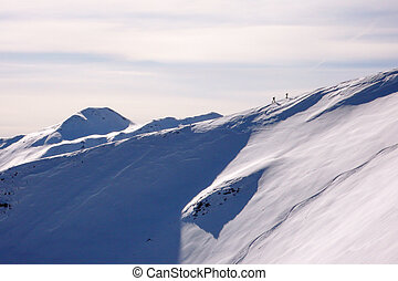 two backcountry skiers hiking up on a long mountain ridge towards the summit near Klosters in the Swiss Alps in deep winter