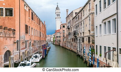 A view of Venice timelapse: canal, bridge, boats and an old tower in the background