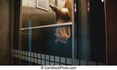 A view of young confident successful businesswoman riding down in transparent elevator using smartphone e-commerce app.