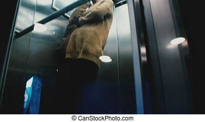 A view of young happy relaxed Caucasian girl riding down in transparent glass wall elevator talking on the phone smiling