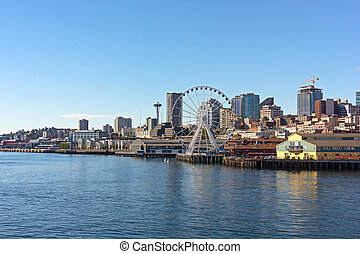 A view on Seattle downtown from the waters of Puget Sound. Piers, skyscrapers and Ferris wheel in Seattle city before sunset.