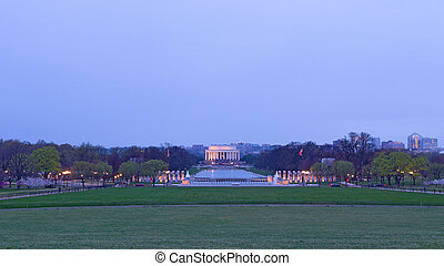 A view on World War II Memorial, reflection pool and Lincoln Memorials at dawn during cherry blossom, Washington DC, USA.