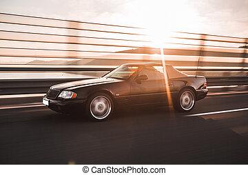 A vintage black sedan car on the bridge in the sunset