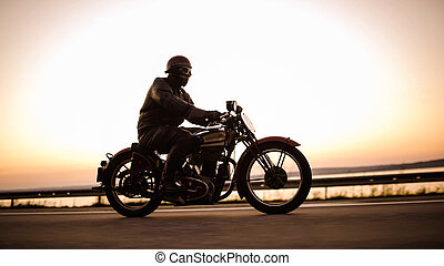 A vintage motorcycle on the street in backlight.