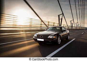 A vintage sedan car on the bridge in the sunset