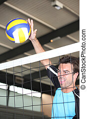 A volleyball player hitting the ball over the net.