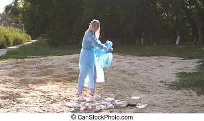 A volunteer girl in gloves collects garbage on the beach in a garbage bag.