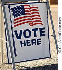 A Vote Here sign in a parking lot. High quality photo