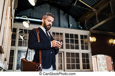 A waist up portrait of businessman with smartphone standing...
