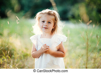 A waist-up portrait of small girl in sunny summer nature. -...