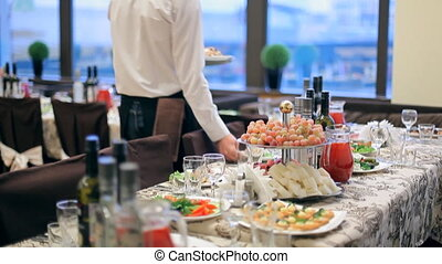 A waiter is carrying dishes to the tables