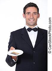 A waiter presenting a credit card.