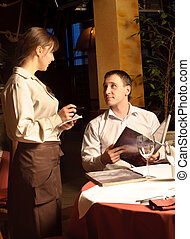 A waiter taking order from restaurant customer