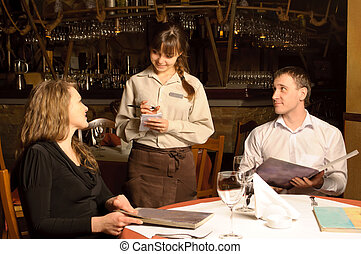A waiter taking order from restaurant customers