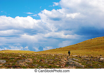 A hiker walks through the tundra in the Rocky Mountains in Colorado