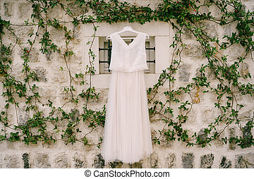 A wall of stone entwined with twisted jasmine branches with a window and a wedding dress in the center.