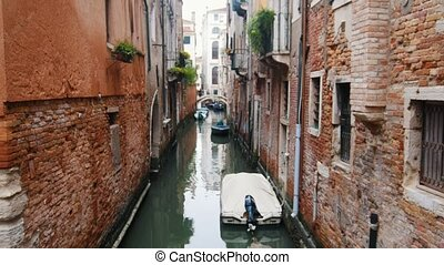 A water canal on narrow streets of Venice. Moored boats. Mid...