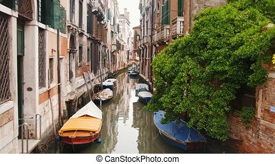 A water canal on the streets of Venice. Moored boats. Mid...