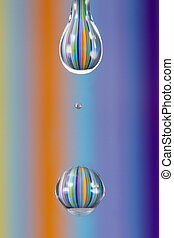 A water drop with colourful stripes reflect from background macro