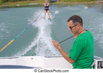 a water skier preforming water skiing sport on a lake