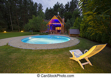A waterpool with chair near wooden house at night