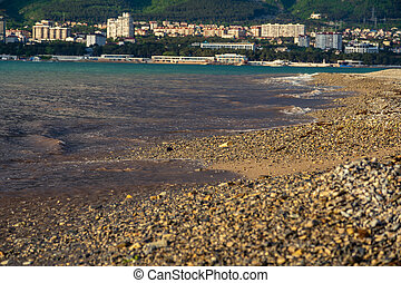 A wave runs over the pebbly beach of the resort town. Sea foam, pebbles. In the background, mountains covered with clouds. City at the foot of the mountains