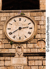 Face of Old Clock on Stone Wall