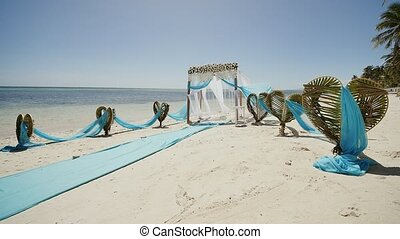 A wedding arch decorated with flowers and large wind-developing fabrics on a tropical beach. Philippines. Bohol.