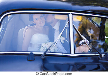 A wedding couple in old car