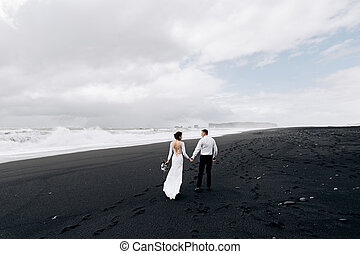 A wedding couple is walking along the black beach of Vic. Sandy beach with black sand on the shores of the Atlantic Ocean. Bride and groom holding hands. Destination Iceland wedding.