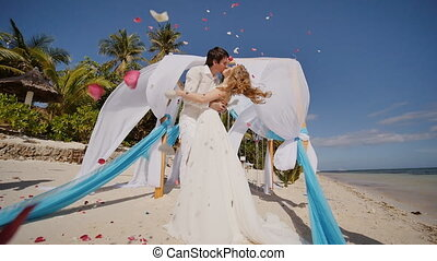 A wedding couple on a tropical beach next to the ocean. Kiss under the arch with white and blue air wings flying in the wind. Around confetti - petals of red roses. Happy together.