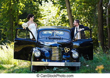 A wedding couple with old car