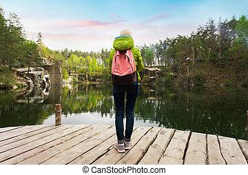 a, weibliche , reisender, gleichfalls, stehende , auf, a, hölzerner pier, bei, a, schöne , see, in, a, kiefer, forest.