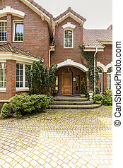 A welcoming entryway with ornamented wooden door, side windows and evergreens in a red brick stylish house. Empty cobbled path in a front.