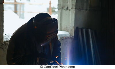 A welder is welding in winter