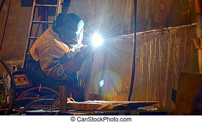 a welder working at shipyard building a ship