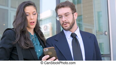 A well dressed man and woman looking at smart phone smiling and talking outside