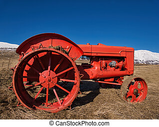 A well preserved oldtimer tractor on the field